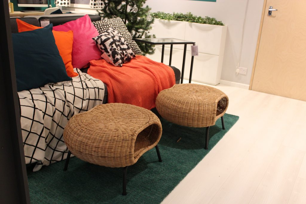 rattan stools, green rug and a sofa covered with colourful throws
