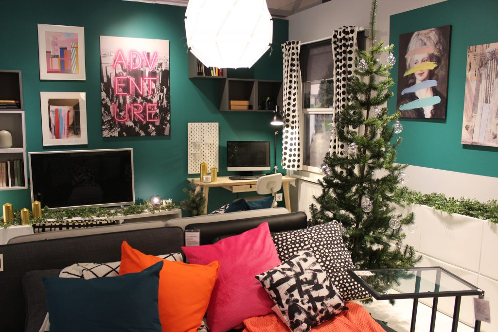 a room with a Christmas tree with a sofa and a green wall, pink art, colourful throws and a lamp. A tv is on a sideboard with festive foliage and a desk with a computer is next to it