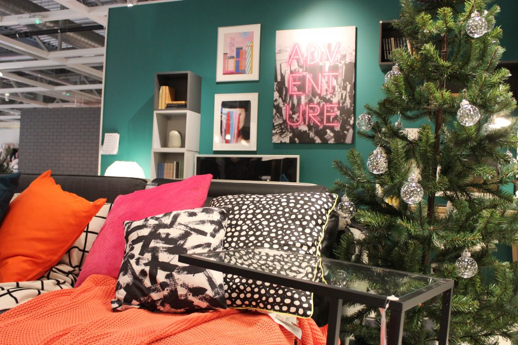 A green wall, pink art, colourful throws and a Christmas trees