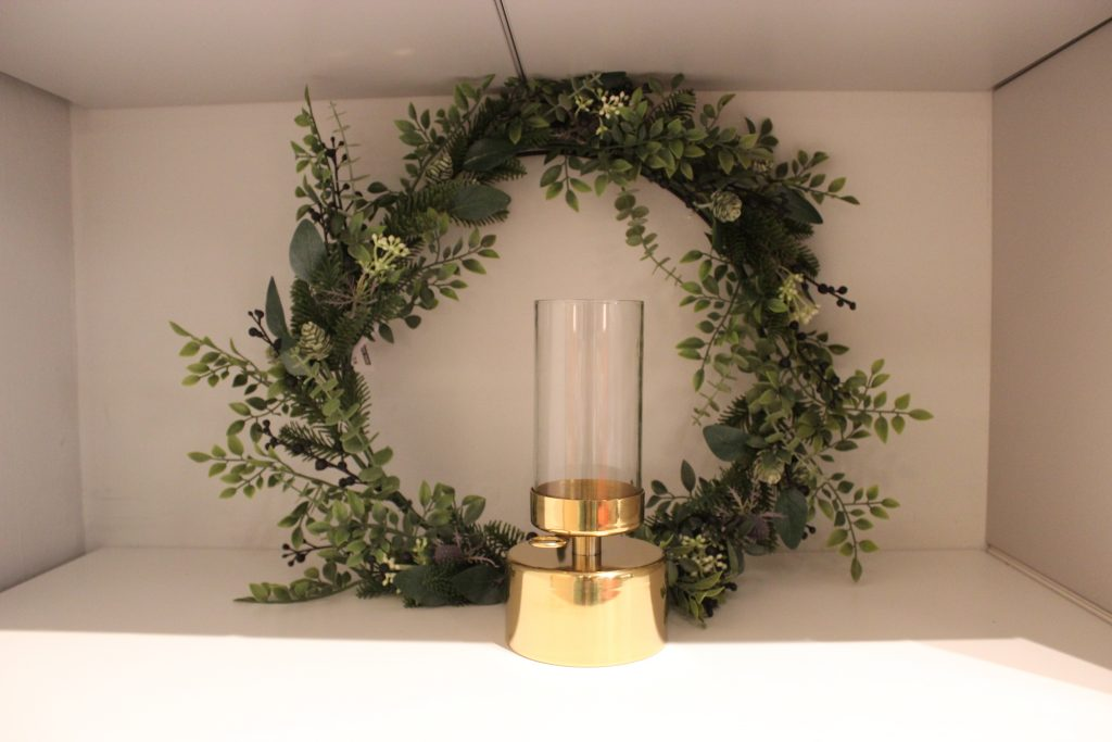 a festive wreath and gold candle lantern