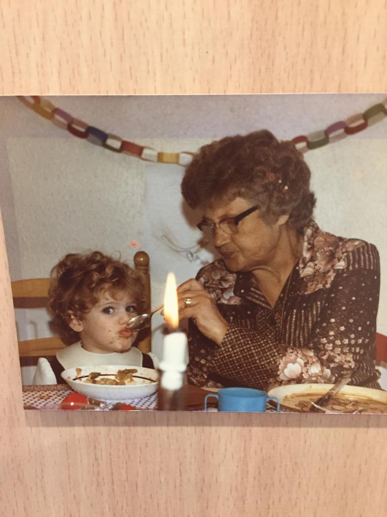 an old photo of a woman in a brown shirt and glasses feeding a small, curly haired child