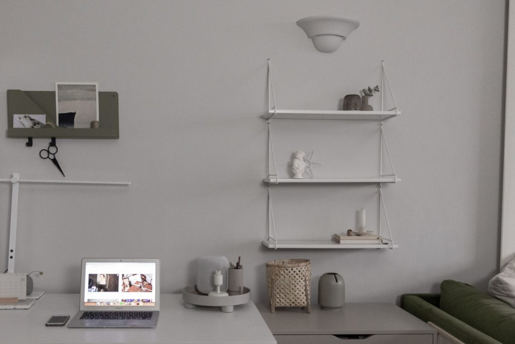 White desk and white shelves on a grey wall