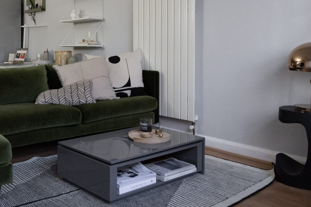 Green sofa and grey table on a grey wall