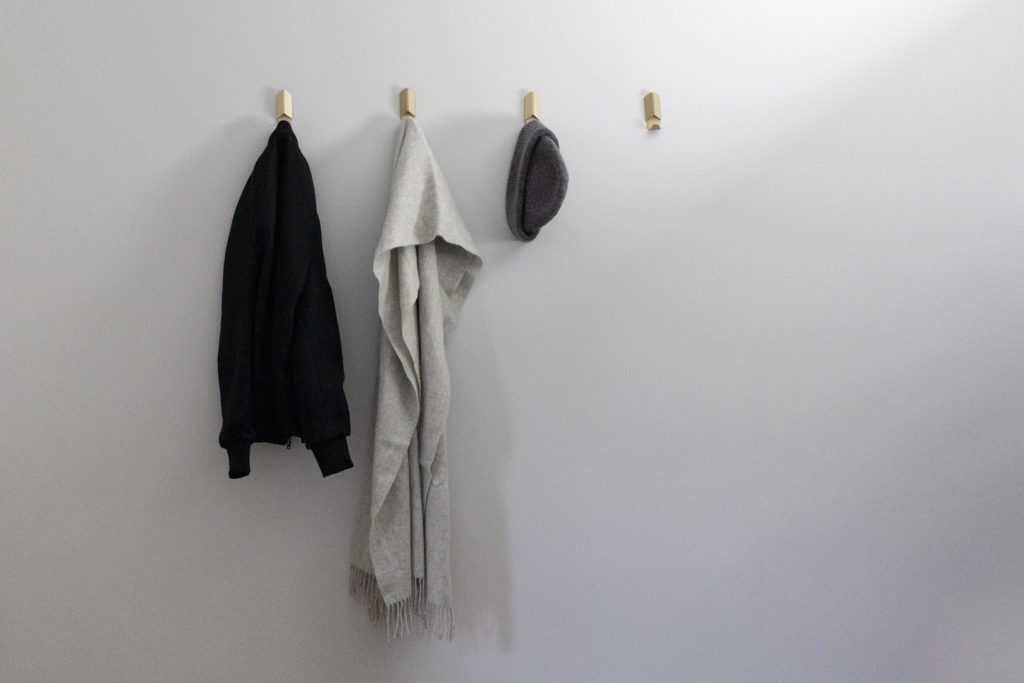 coats hanging on a grey wall