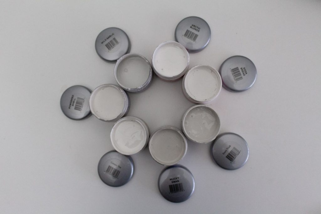 A circle of tester pots with their lids off