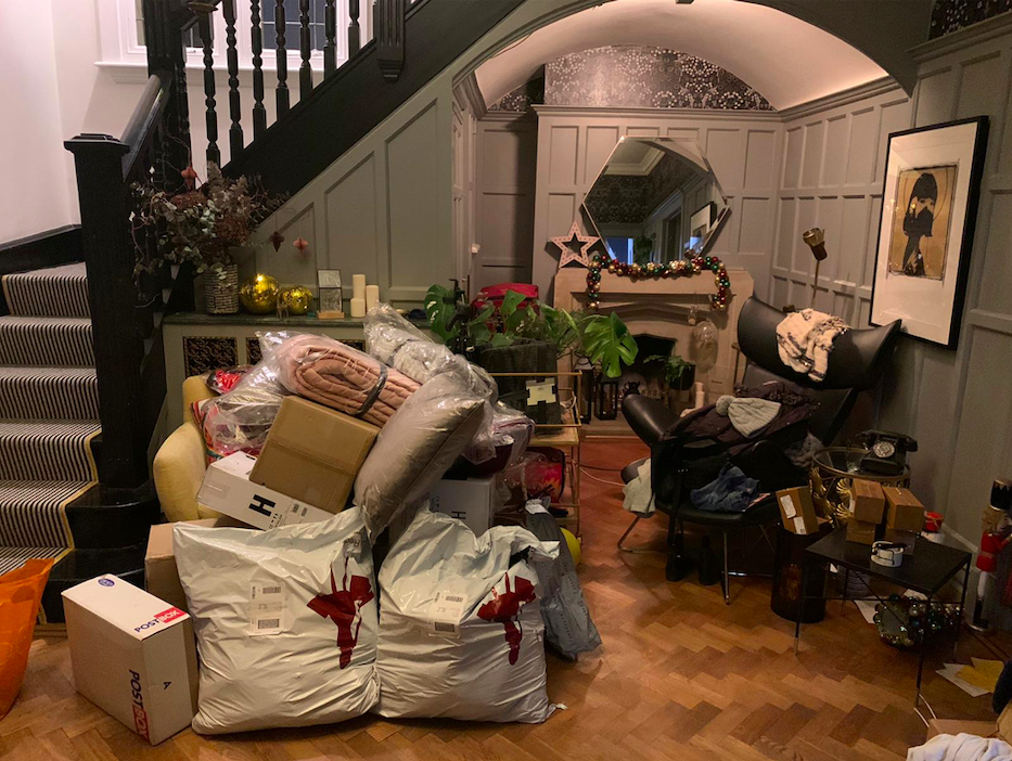 a large landing with a chair, lots of bags and boxes, a fireplace and staircase