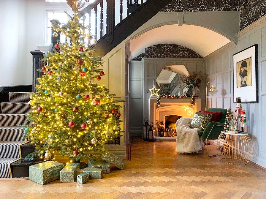 a large landing with a chair, christmas tree, fireplace and staircase