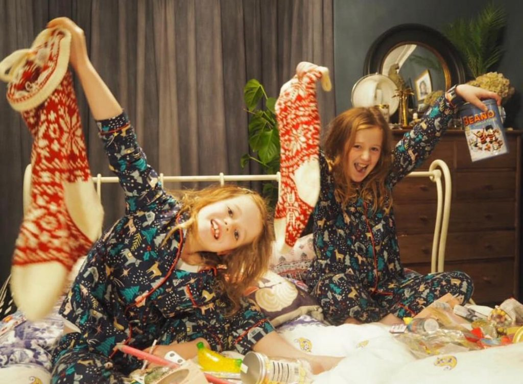 Two children in matching patterned pyjamas hold up red christmas stockings while sitting in bed