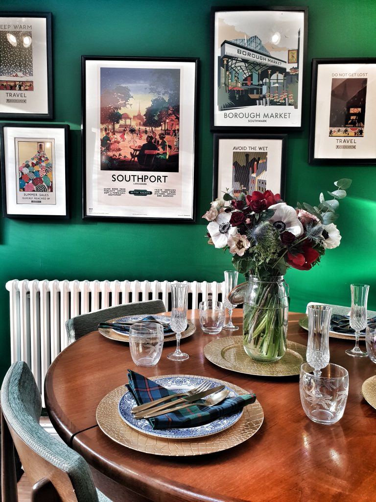a green wall with travel prints. festive table with tartan cloth, flowers, gold plates and champagne flutes