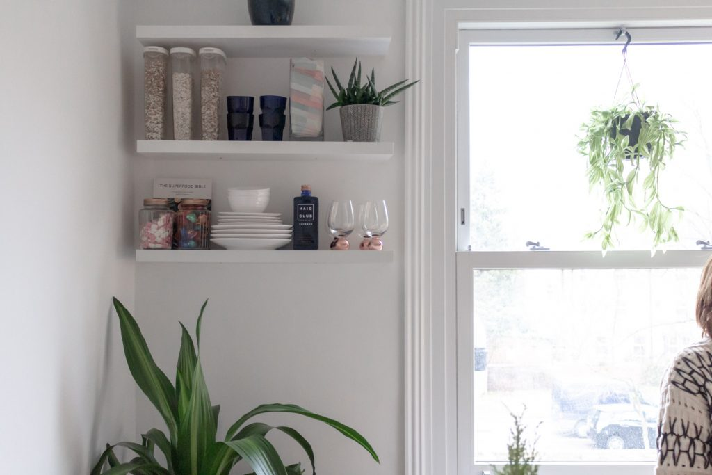 Image shows a kitchen shelf with some whisky and jars on it, next to a bright window