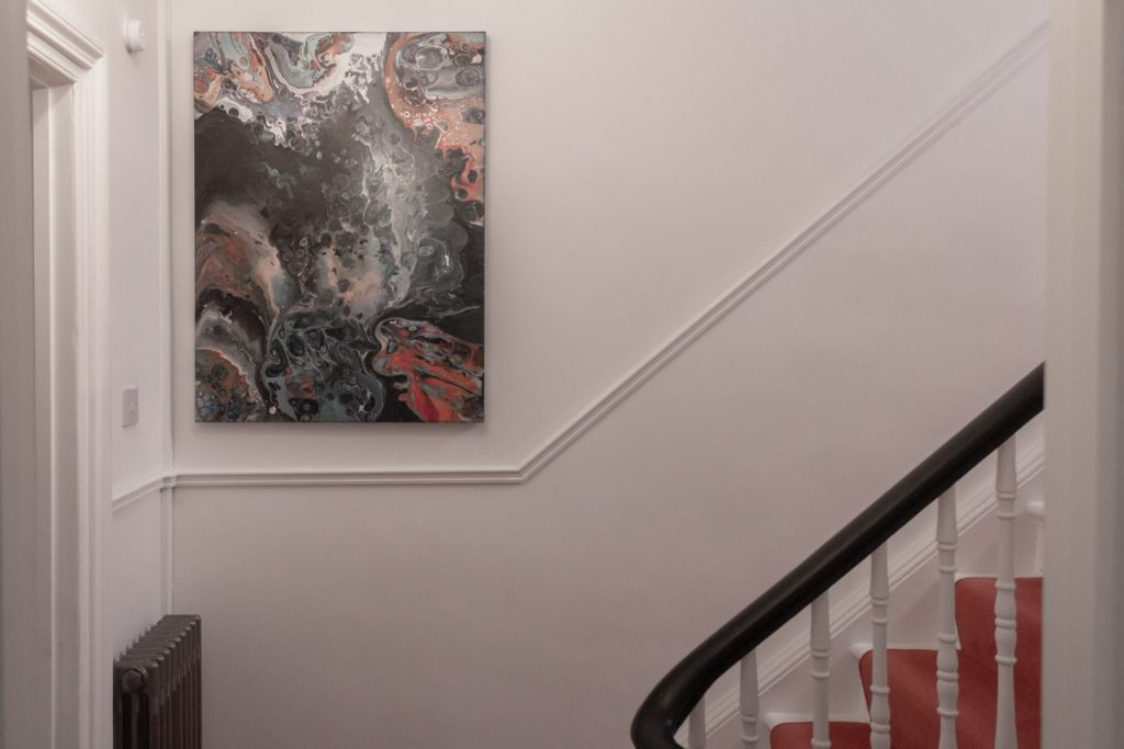 Image shows a swirly painting hanging at the bottom of some white stairs with an orange carpet