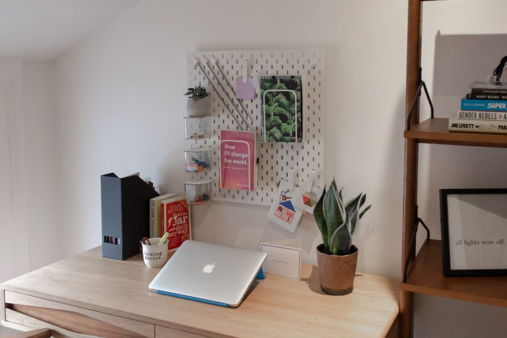 Image shows a wooden desk with a laptop and some self-help books on it