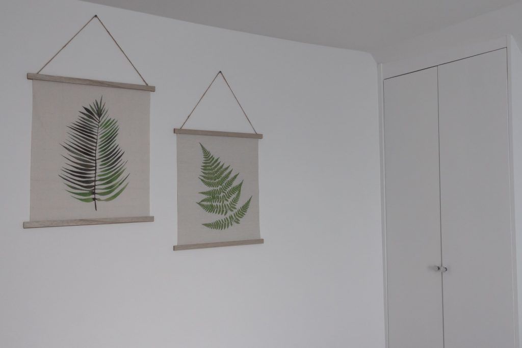 Image shows two fern prints on a white wall