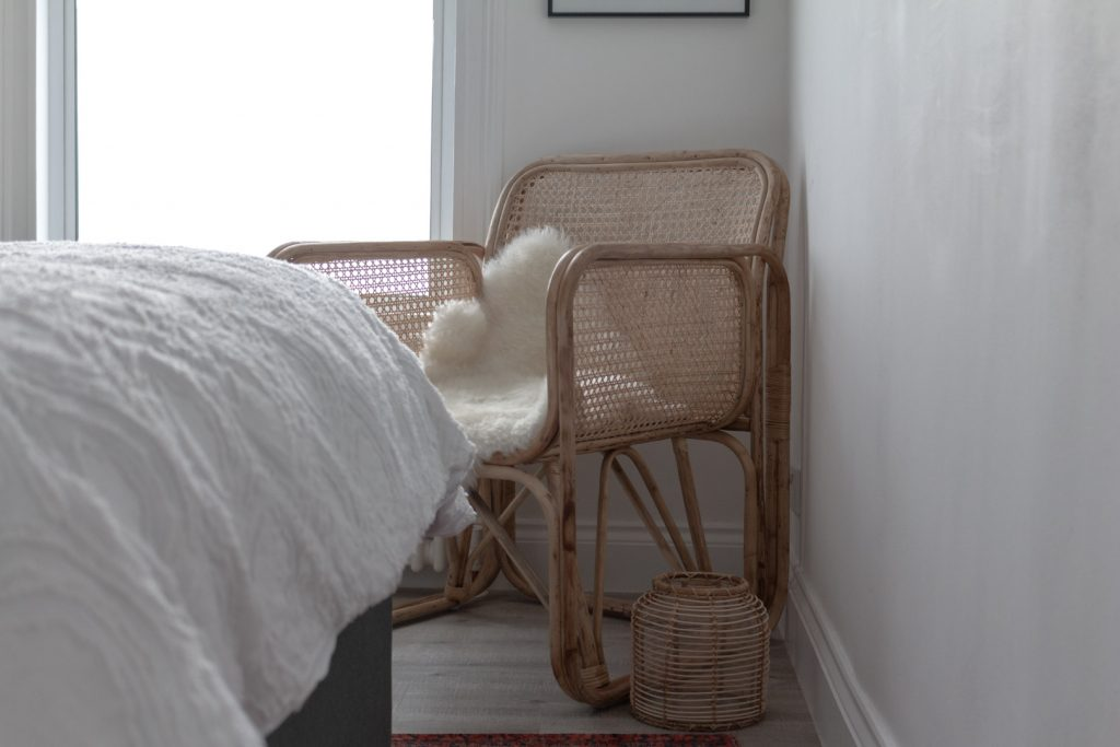 Image shows a rattan chair i the corner of a white room