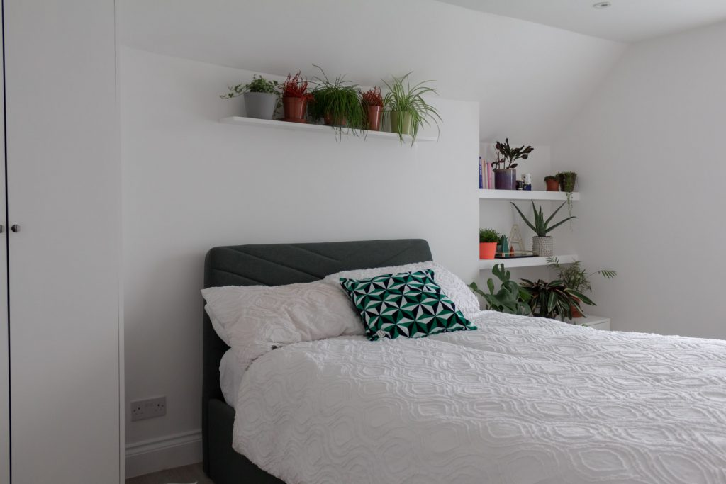 Image shows a white wall behind a bed in all-white covers