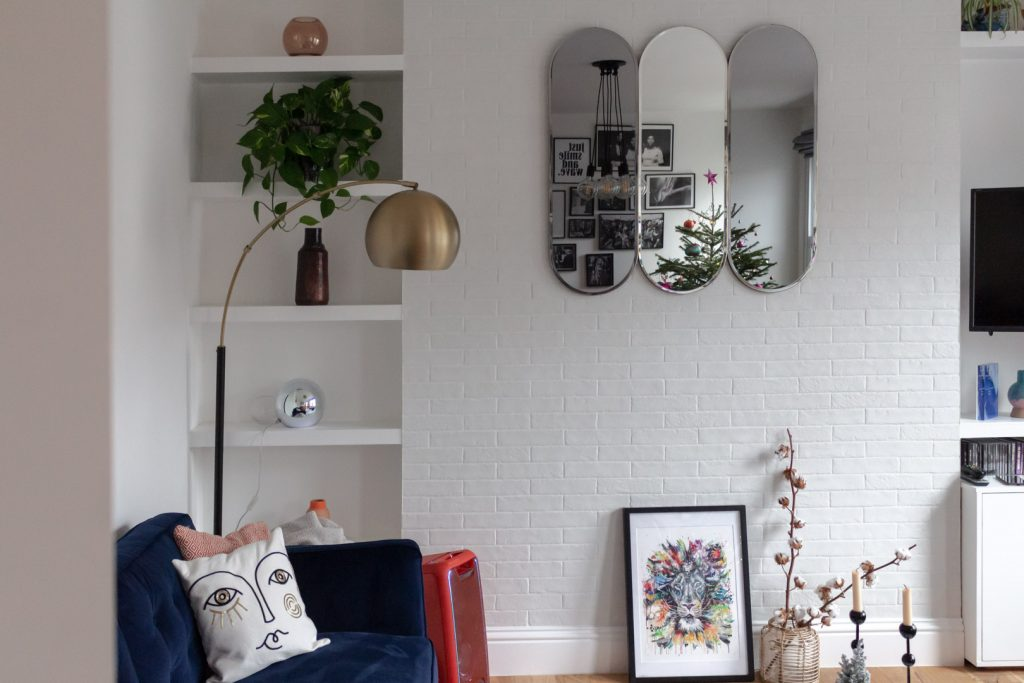 Images shows a three-part mirror on a white brick wall