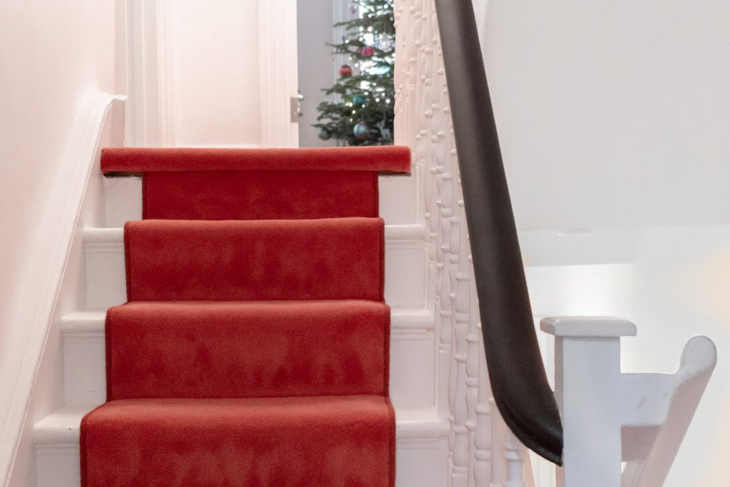 A rich orange carpet runs up some white stairs with a dark wood bannister