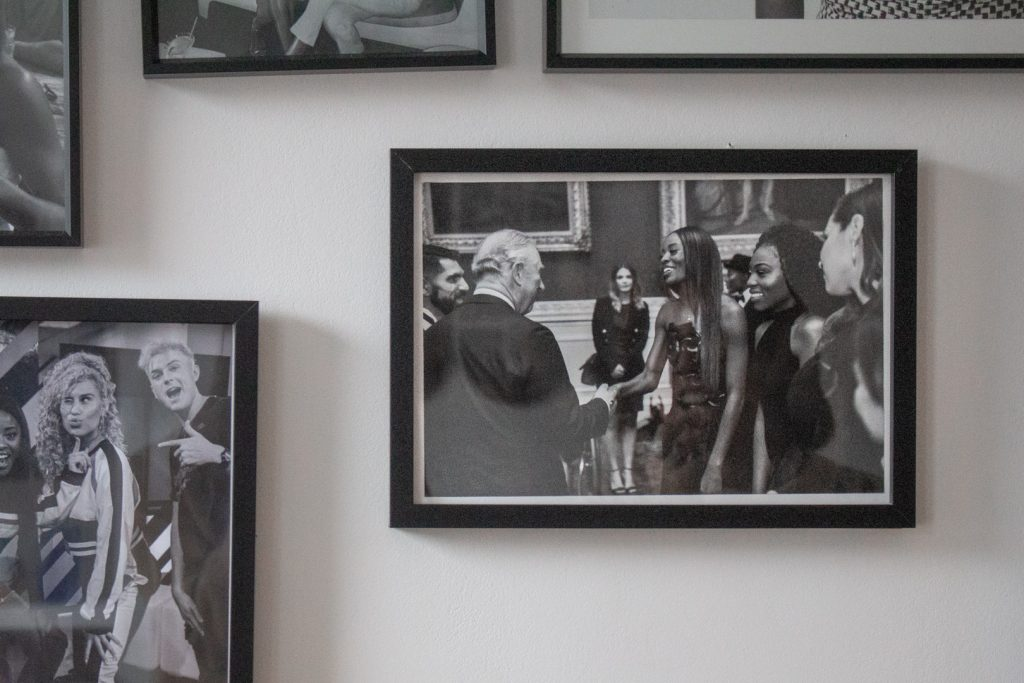 Image shows a black and white photograph of a woman shaking hands with prince charles