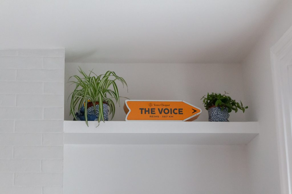Image shows a white shelf with a champagne box the says The Voice on it