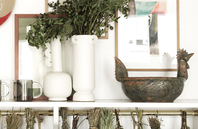 Image shows some white vases holding greenery, next to a bowl shaped like a chicken (yes, really) on a white shelf