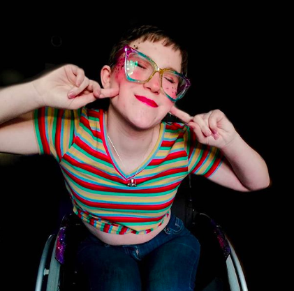 zoe smiles in a stripey T-shirt, with bright glasses and her hands at her face