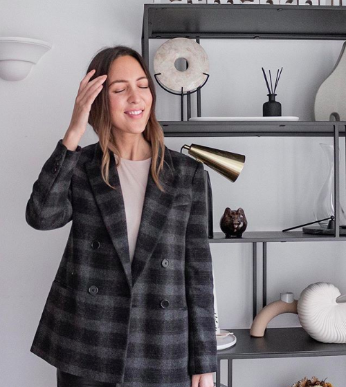 Emma stands in a grey check blazer touching her head and smiling, in front of a grey wall with black shelves on them