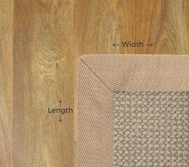A beige rug with a beige herringbone trim sits on a pale hardwood floor
