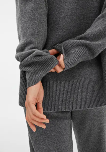 a hand plays with a grey jumper