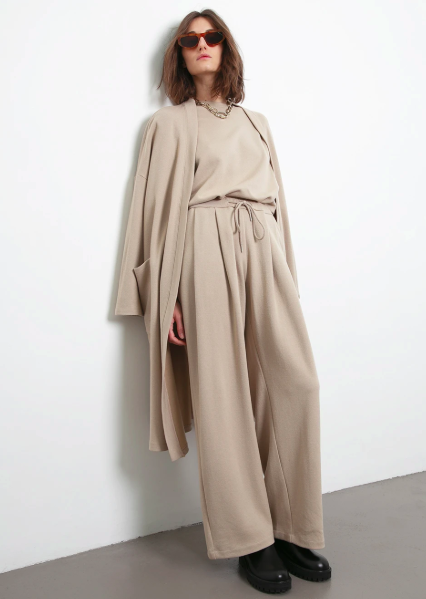 a woman dressed in all-beige loungewear leans on a wall