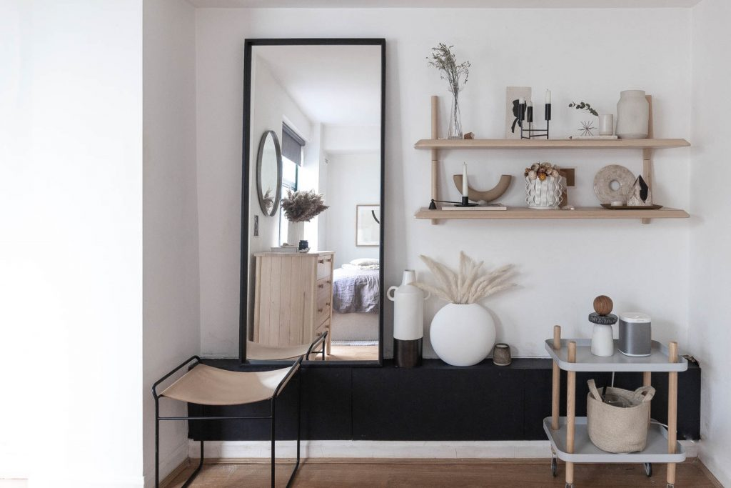 A large mirror stands on a black shelf, with a tan leather stool in front of it. Next to the mirror is a couple of shelves with lots of lovely things in shades of bacl and brown