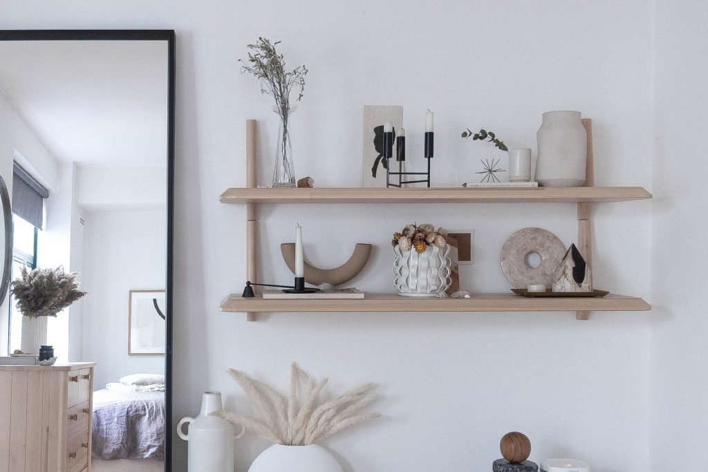 An array of black, white and tan objects sit on a couple of pale wood shelves