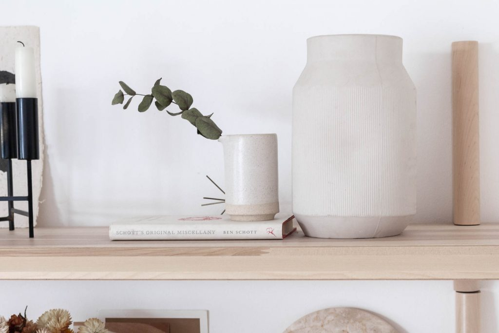 A close up on one end of an ash wood shelf with a cream ceramic vase and a small ceramic jug with a sprig of dried eucalyptus in it