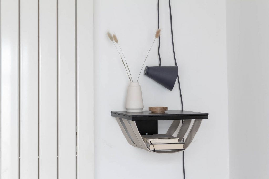 A dark grey light on a trailing wire hangs above a black wall shelf with sand coloured leather straps hanging under it