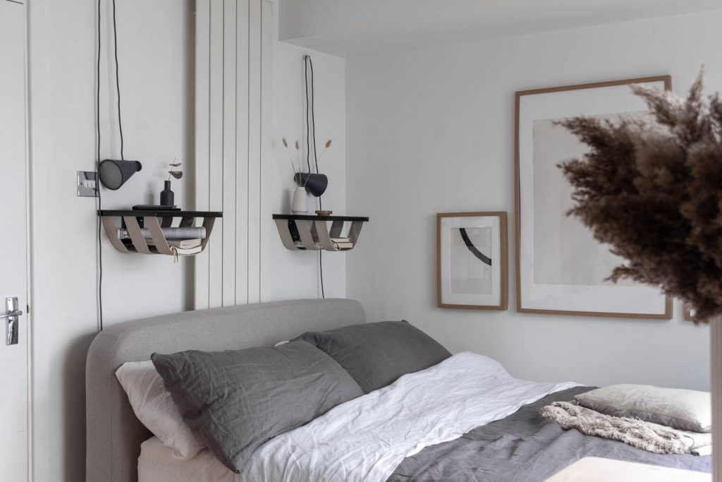 The corner of a bedroom. You can see the head of a grey fabric bed and above the bed are two balack shelves with sand coloured leather straps underneath, holding books