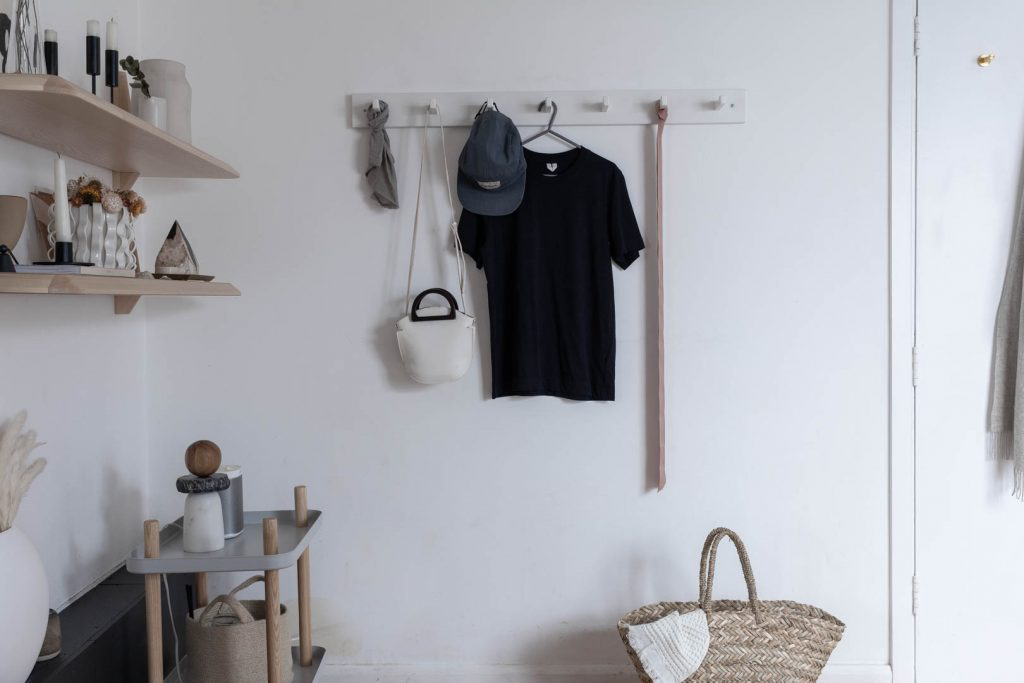 A set of white hooks on a white wall, with handbags, hats and a navy T-shirt hanging on them