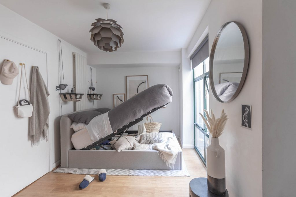 A grey fabric bed with the ottoman top lifted sits in a room with white walls. On the wall is some minimal circle art, and above the bed is a grey lightshade shaped like a minimal artichoke