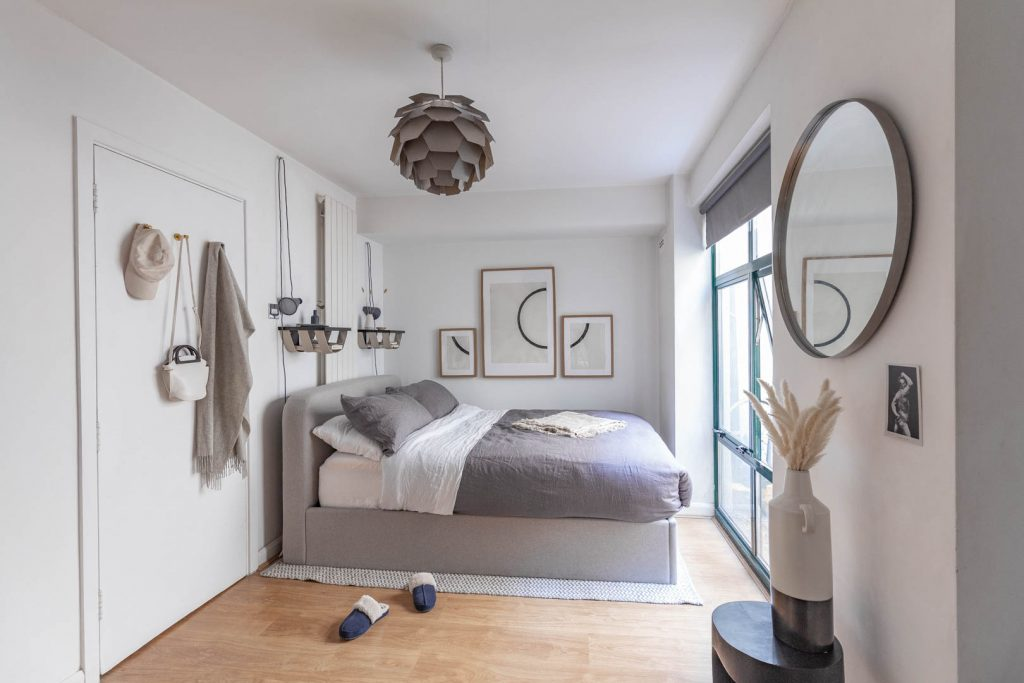 A grey fabric bed sits in a room with white walls. On the wall is some minimal circle art, and above the bed is a grey lightshade shaped like a minimal artichoke