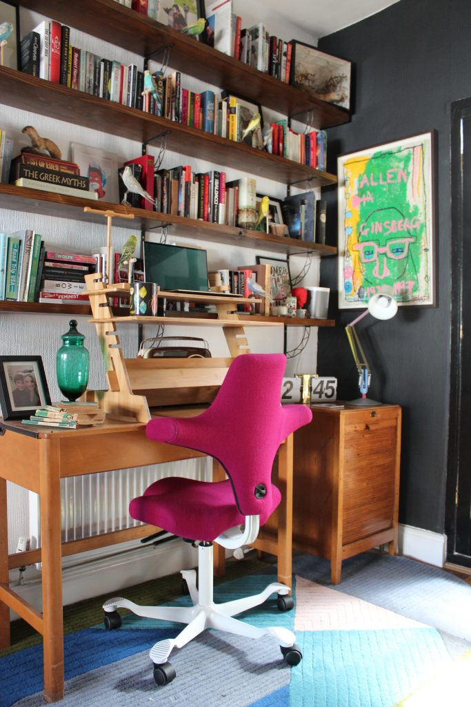 A Colourful home office with a bookshelf full of multi coloured books, a rug that's green blue and pink and a pink chair. vintage wooden desk with standing desk adaptor all in front of a black framed glazed door