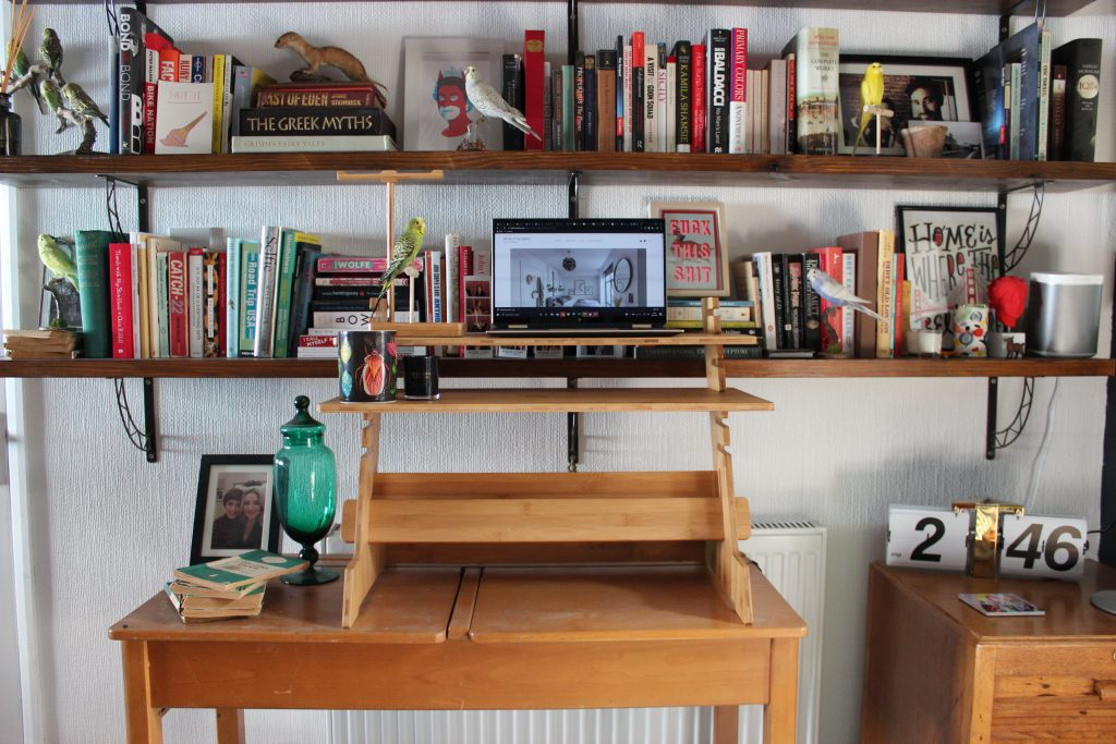 A Colourful home office with a bookshelf full of multi coloured books, a rug that's green blue and pink and a pink chair. vintage wooden desk with standing desk adaptor with a laptop on it and a green glass vase and green books next to it.