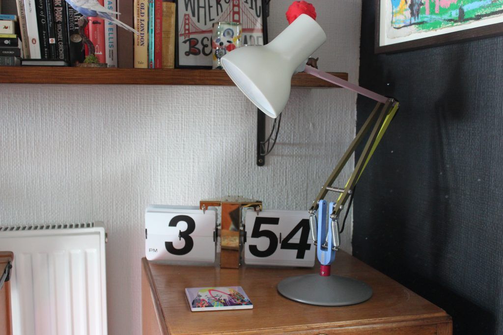 a multi coloured anglepoise lamp, a flip clock and a coaster on a wooden table with a shelf of books above and a black wall behind.