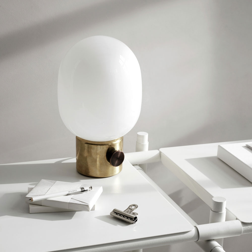 A lamp sits on a white desk in front of a white wall, and the desk has all white things on it, including a stack of envelopes, white pen and silver bulldog clip. The lamp is an oval-shaped white glass orb on a round brass base with a round turny-knob on it.