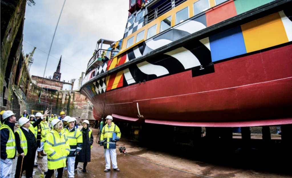a boat is painted wit multicoloured patterns. Many people in reflective jackets and hard hats look on