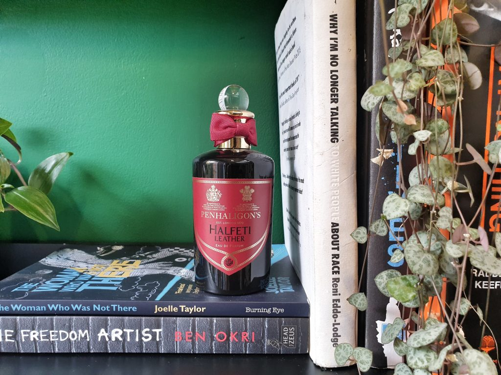 A black perfume bottle with a red label reading Penhaligons Halfeti Leather on a stack of black books from Joelle Taylor and Ben Okri on a black shelf against a green wall with a plant down hanging down over a stack of books that are white and black and orange.