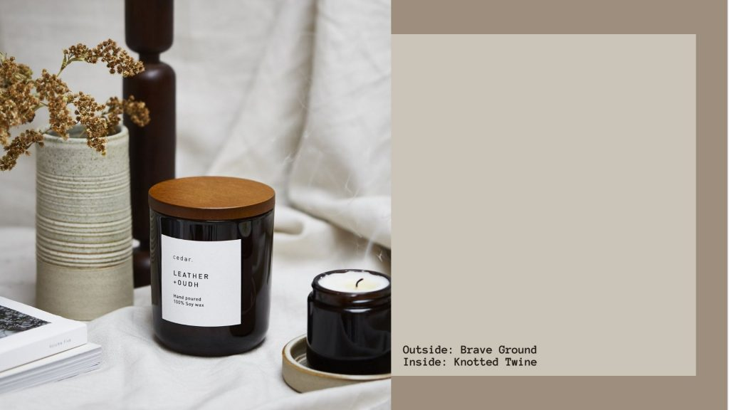 Image shows the Cedar Leather & Oudh candle on one side, with a colour swatch of Brave Ground (a rich greige) and Knotted Twine (a lighter greige)