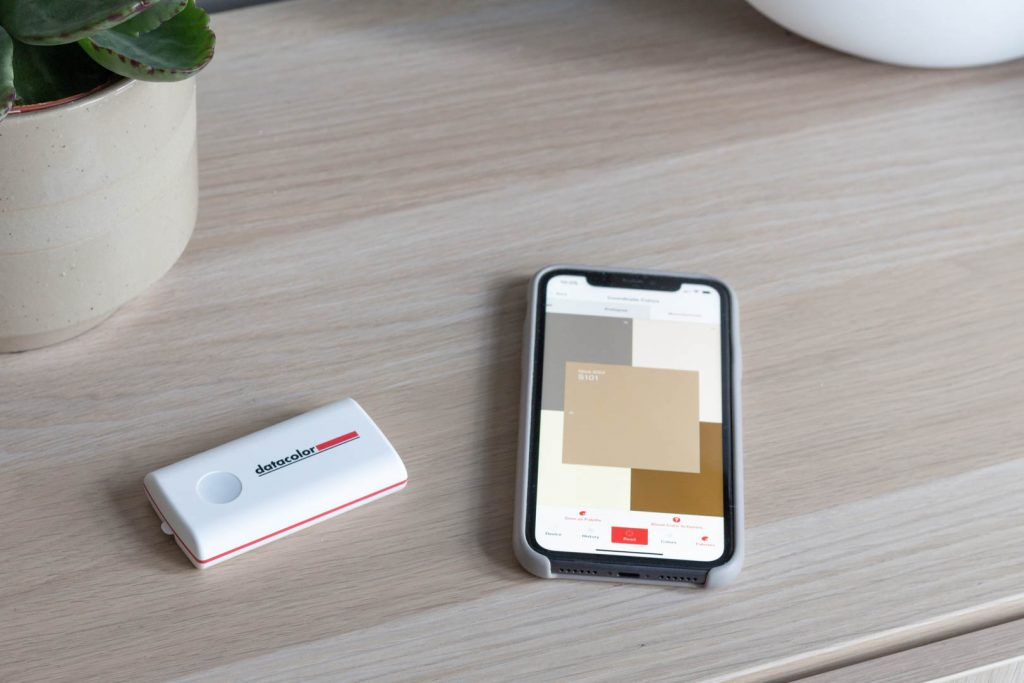 The colour picker - a white plastic oblong with a button at one end, sits next to a phone displaying a colour paelette of nudes and browns