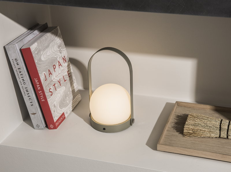 An image of the menu carrie lamp on a white shelf next to some books