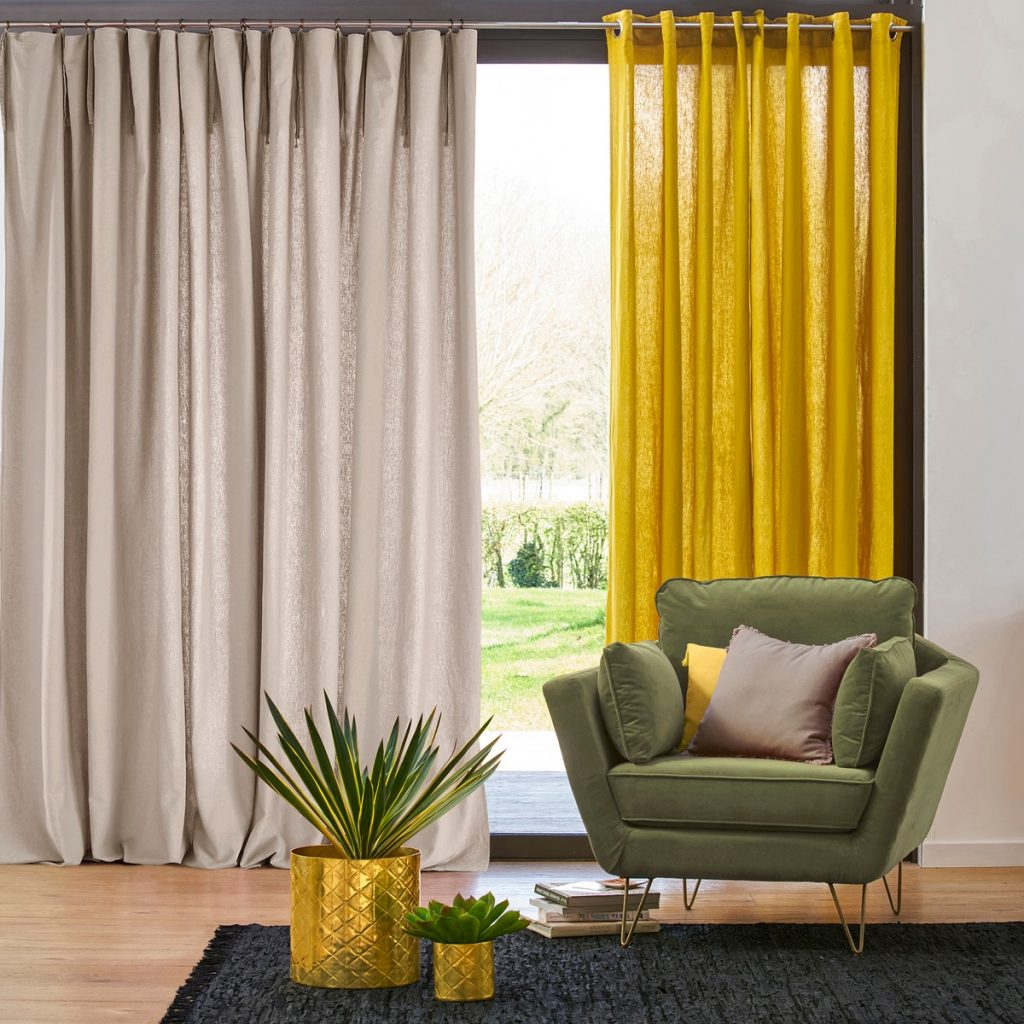two different curtains hanging at a full-length window. One is beige linen, the other is yellow. We mainly focus on the beige one