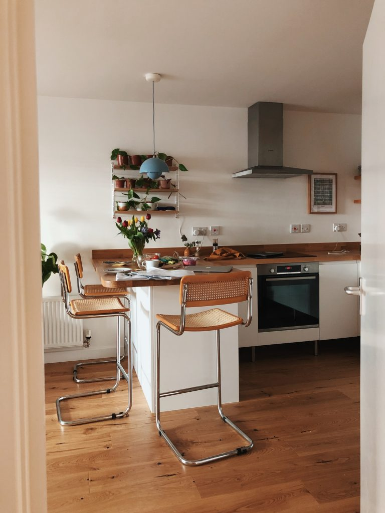 a white kitchen with white units. There's a breakfast bar with tall cane and metal chairs. There are flowers on the counter and papers and cups. A set of shelves above the worktop holds plants in pots.