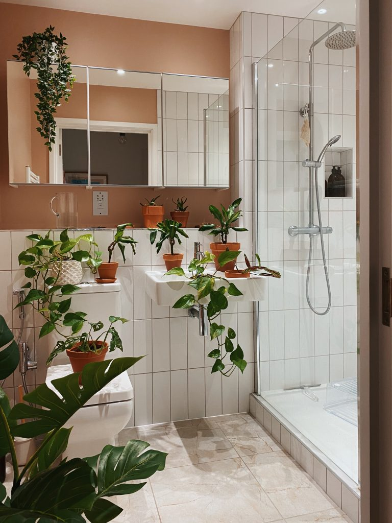a bathroom with beige walls and white tiles in a shower cubicle. There are shelves with plants on all over and a large mirrored cabinet unit on the wall.