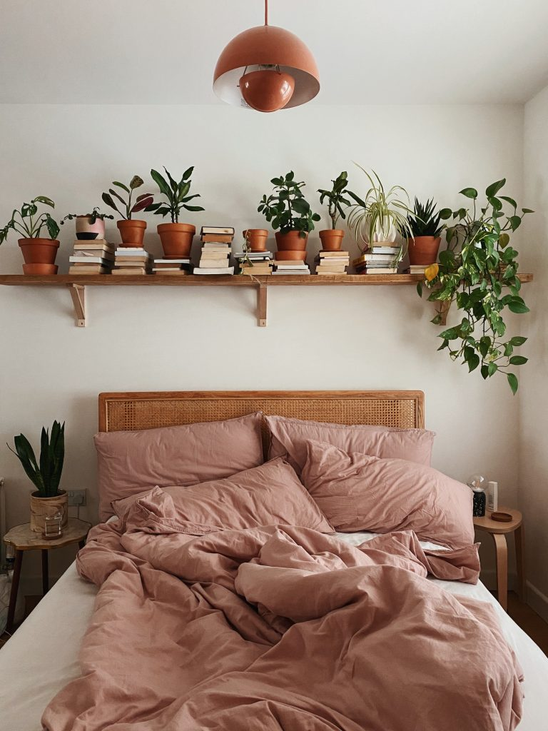 unmade bed with taupe bedding on a white wall. A shelf above it has lots of plants on.
